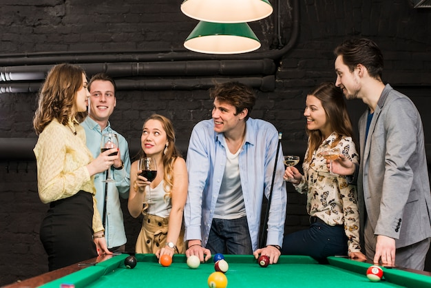 Smiling couples in club enjoying snooker and drinks Free Photo