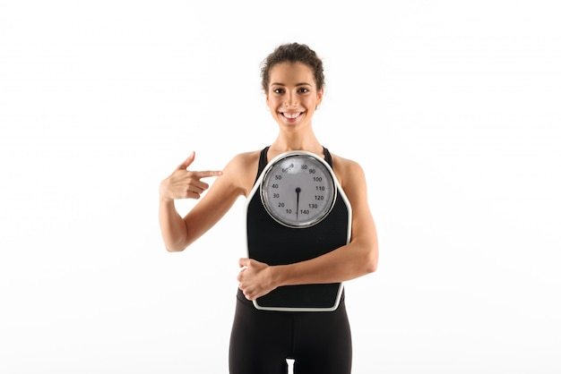 Smiling curly brunette fitness woman holding weighting scales Free Photo