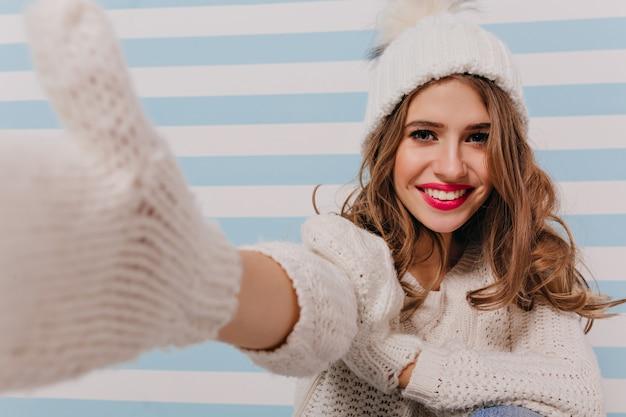 笑顔の巻き毛のスラブモデルで、セルフィーを撮る優しいメイク。縞模様の青い壁にニットの服を着た女の子の肖像画 無料写真