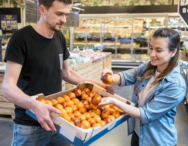Smiling customers buying sicilian oranges in grocery section Free Photo