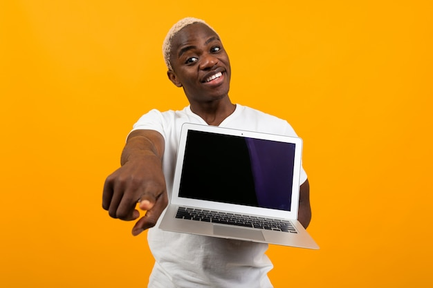 Smiling cute american in white t-shirt showing laptop display with mockup and pointing finger forward on orange studio background Premium Photo