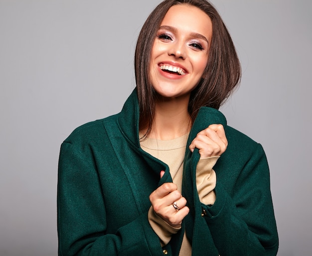Smiling cute brunette woman in casual green jacket on gray Free Photo