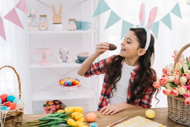 Smiling cute girl with bunny ears over her head eating chocolate easter egg Free Photo