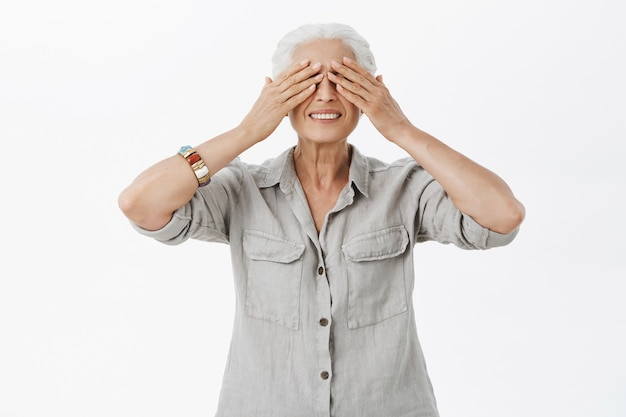 Smiling cute old lady shut eyes with hands and waiting for surprise Free Photo