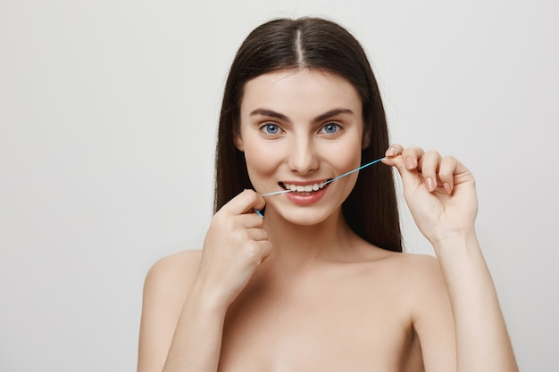 Smiling cute woman flossing teeth with dental floss Free Photo
