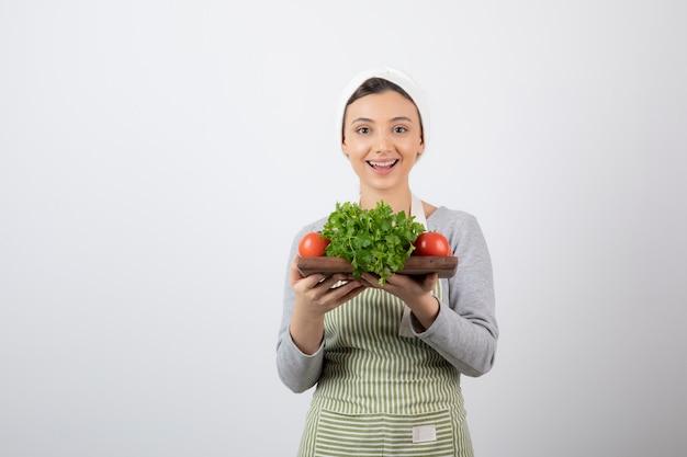 Улыбается милая женщина модель держит деревянную доску со свежими овощами. Бесплатные Фотографии