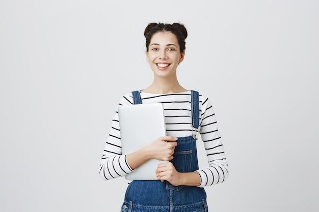Улыбающийся милый молодой программист, девочка-подросток начинает кодировать, держит ноутбук и выглядит довольным Бесплатные Фотографии