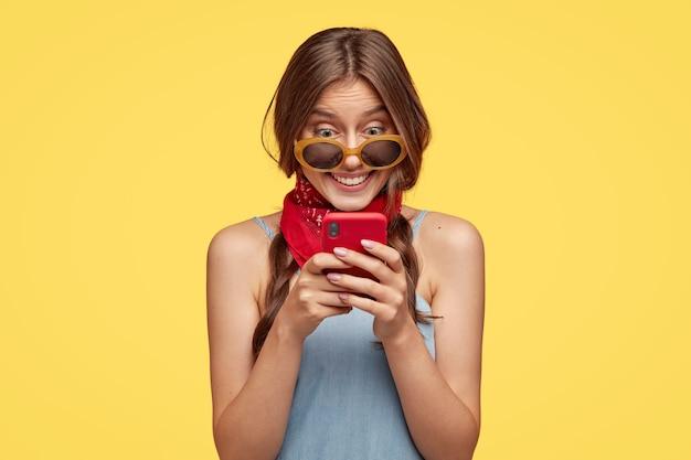 Sorridente donna dai capelli scuri con espressione allegra, tiene il telefono cellulare rosso, felice di leggere il messaggio di testo, connesso a internet wireless, isolato sopra la parete gialla. persone, tecnologia, tempo libero Foto Gratuite