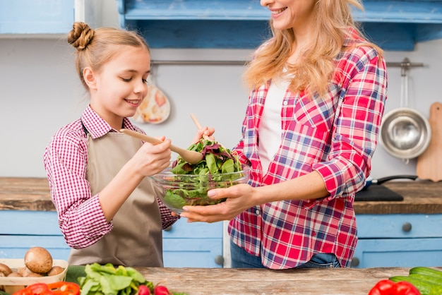 Smiling daughter and mother preparing the leafy vegetable salad in the kitchen Free Photo