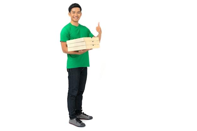 空白のtシャツの制服を着た笑顔の配達人の従業員がクレジットカードで立って食べ物を注文し、ピザの箱を分離して保持している Premium写真