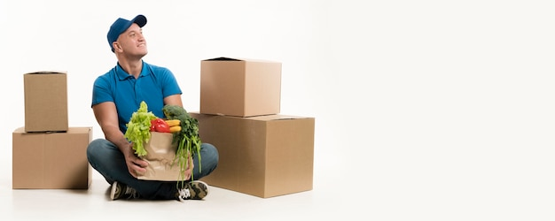 Smiling delivery man holding grocery bag Free Photo