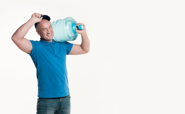 Smiling delivery man holding water bottle and cap Free Photo
