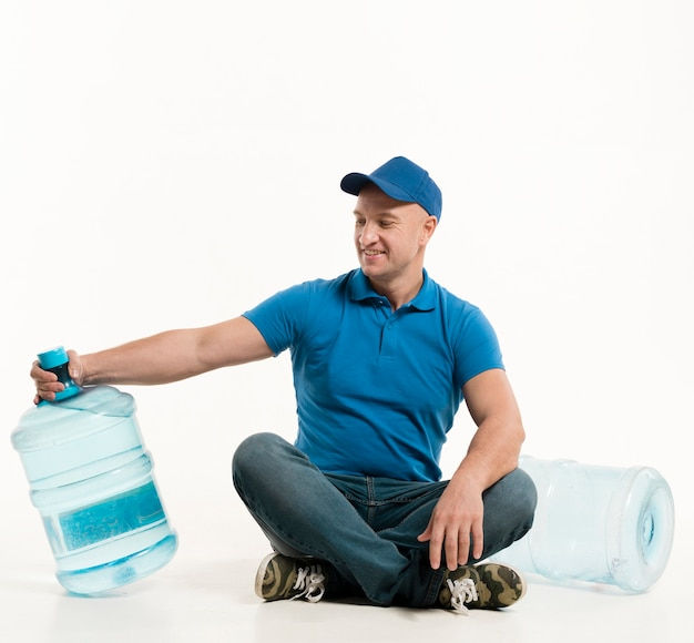 Smiling delivery man looking at water bottle Free Photo