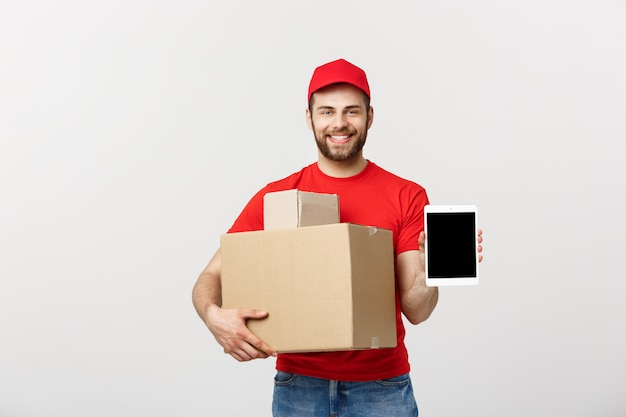 Smiling delivery man presenting tablet and holding boxes in his hand. Premium Photo