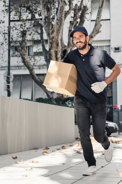 Smiling delivery man running on pavement with parcel Free Photo