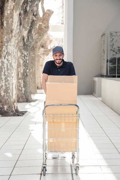 Smiling delivery man walking on pavement with trolley full of cardboard boxes Free Photo