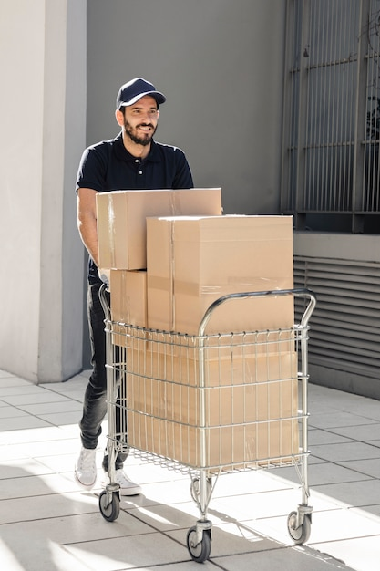 Smiling delivery walking on pavement with trolley full of cardboard boxes Free Photo