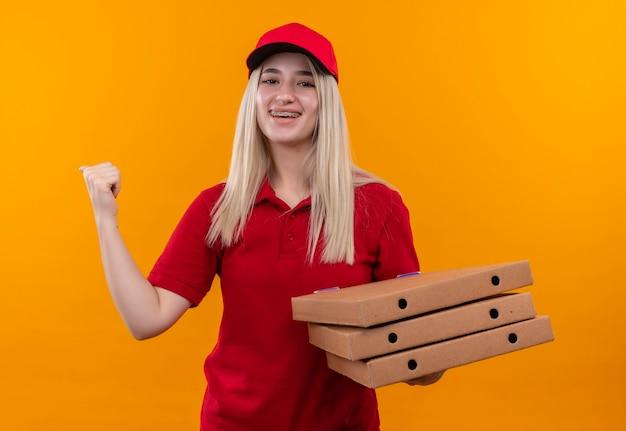 孤立したオレンジ色の背景にイエスのジェスチャーを示す赤いtシャツとピザボックスを保持しているキャップを身に着けている笑顔の配達の若い女の子 無料写真