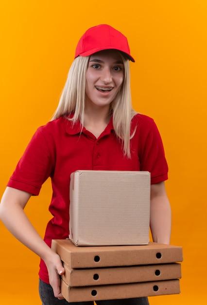 孤立したオレンジ色の背景に歯科ブレース保持ボックスとピザボックスで赤いtシャツとキャップを身に着けている笑顔の配達の若い女の子 無料写真