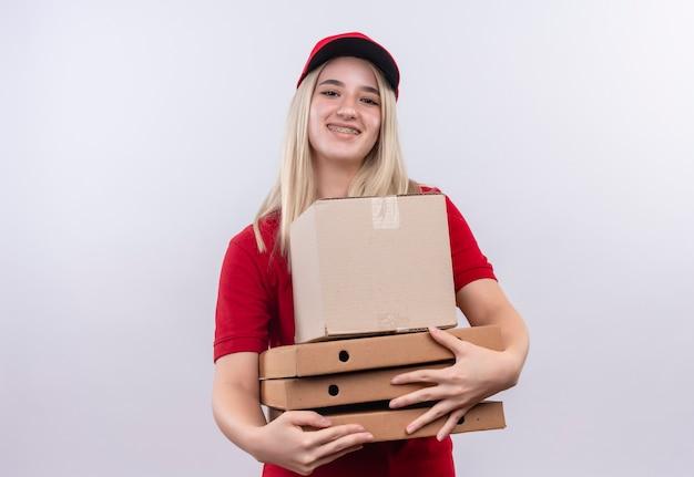 孤立した白い背景の上の歯科ブレース保持ボックスとピザボックスで赤いtシャツとキャップを身に着けている笑顔配達少女 無料写真
