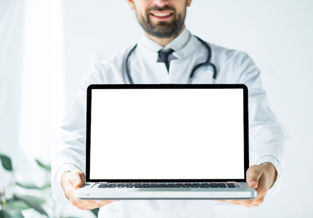 Smiling doctor demonstrating laptop Free Photo
