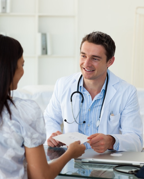 Smiling doctor giving a prescription to his female patient Premium Photo