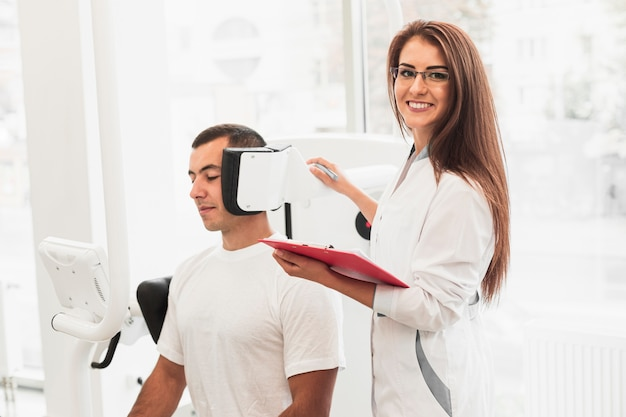 Smiling doctor holding clipboard checking patient Free Photo