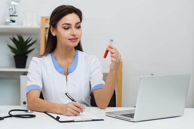 Medico sorridente che esamina un campione di sangue Foto Gratuite