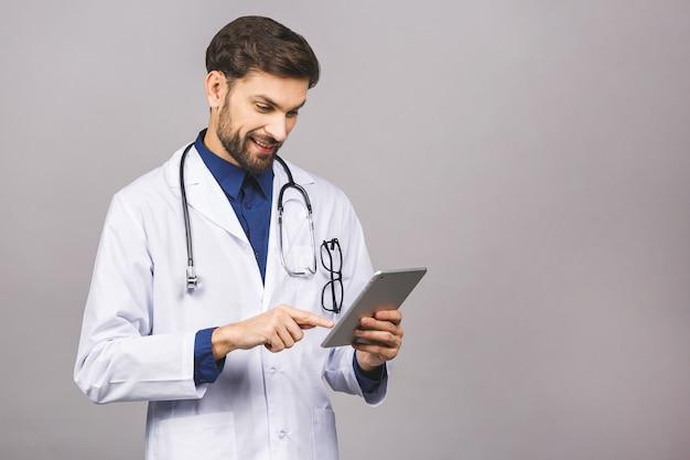 Улыбающийся доктор с помощью планшетного компьютера Premium Фотографии