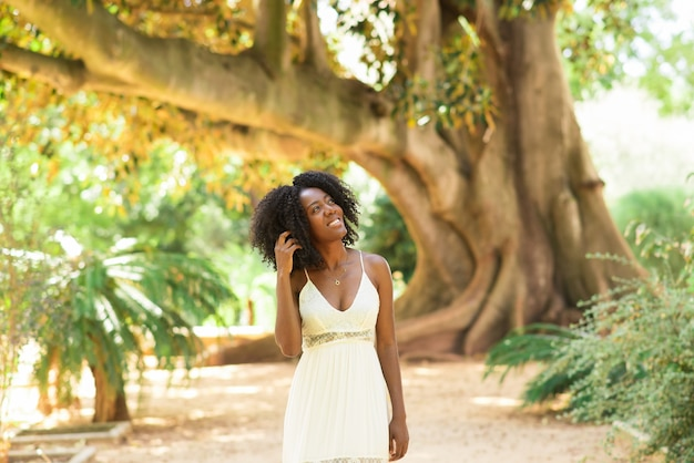 Smiling dreamy black woman walking in park Free Photo