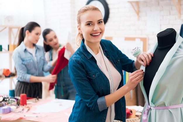 Smiling dressmaker near dress with mannequin Premium Photo