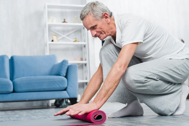 Smiling elder man rolling yoga mat after yoga in home Free Photo