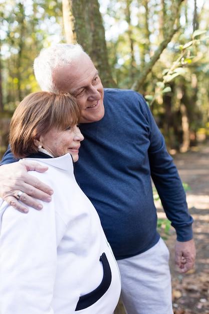Улыбаясь пожилая пара позирует в парке Бесплатные Фотографии