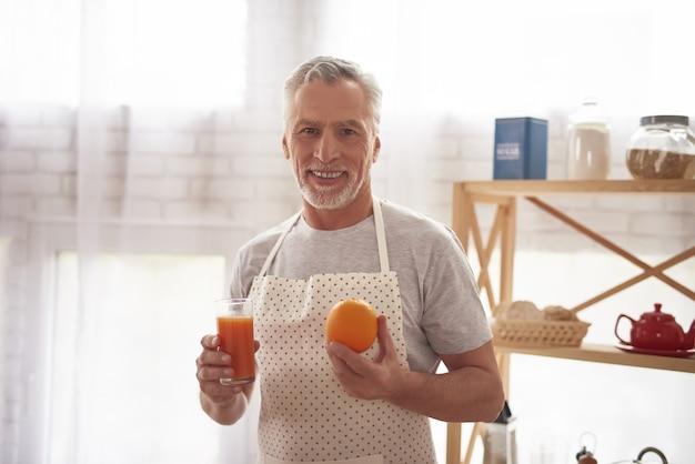 Smiling elderly man holds orange juice in kitchen. Premium Photo