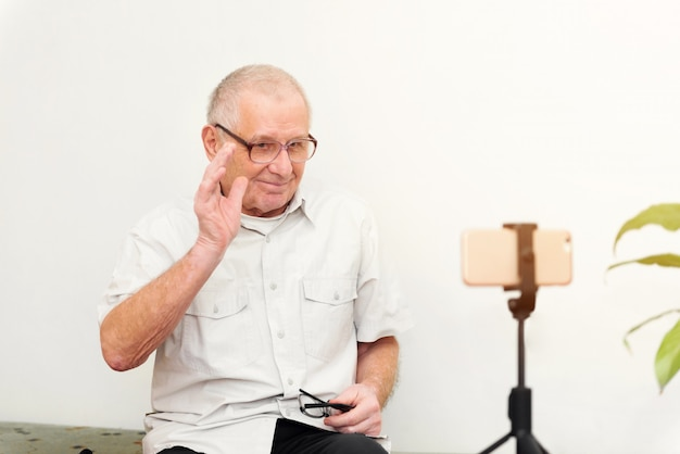 Smiling eldery man looking at camera making video blog or call at home sitting on sofa dating online headshot portrait Premium Photo