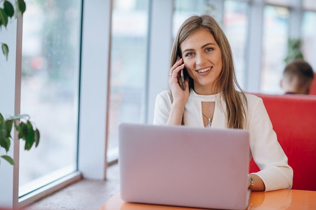 Smiling elegant woman talking on the phone and looking ahead Free Photo