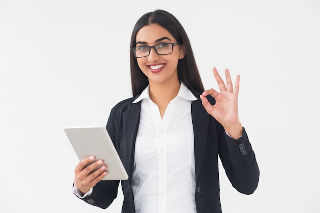 Smiling elegant woman with tablet showing ok sign Free Photo