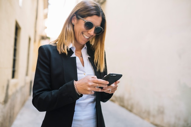 Smiling elegant young woman using smartphone between buildings on street Free Photo