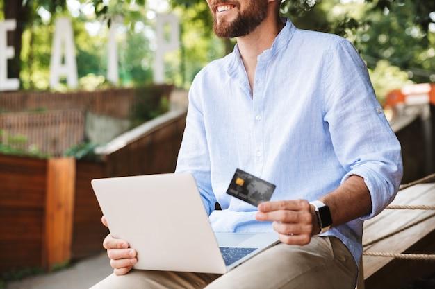 ノートパソコンを使用して感情的な若いひげを生やした男の笑顔 Premium写真