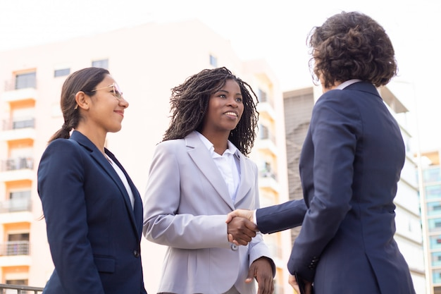 Smiling employees shaking hands on street. cropped shot of young multiethnic businesswomen meeting outdoor. business Free Photo