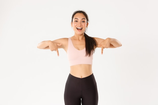 Smiling energized asian fitness girl, female athlete inviting for event, showing workout gear advertisement, pointing fingers down, your logo banner. Premium Photo