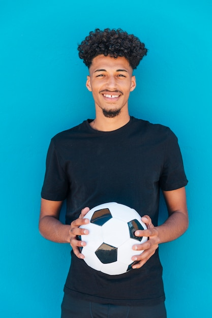 Smiling ethnic guy standing with football Free Photo