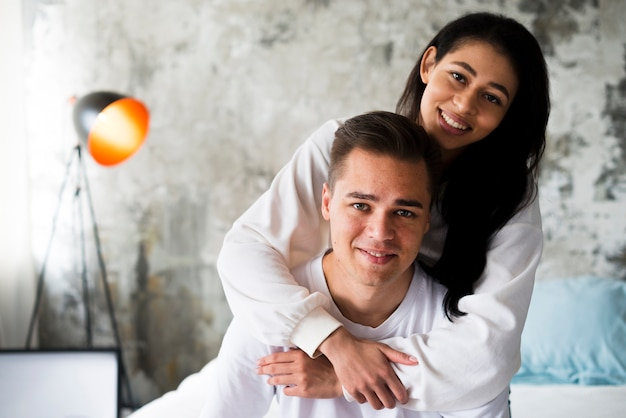 Smiling ethnic woman in white clothes hugging handsome man from behind Free Photo
