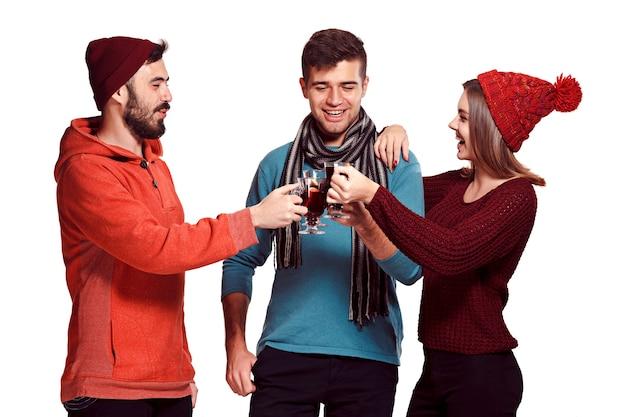 パーティーの写真撮影中にヨーロッパの男性と女性を笑顔。フォアグラウンドでホットホットワインとワイングラスを持ってスタジオフェストで友達を装った男たち。 無料写真
