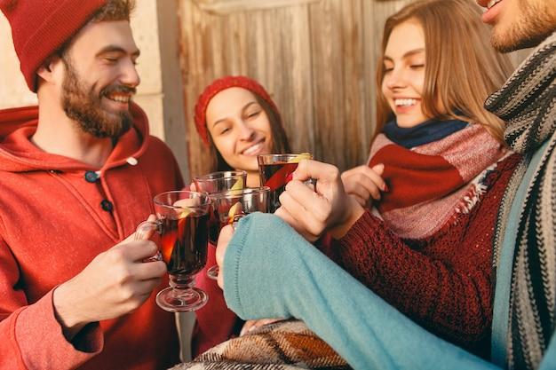 파티 사진 촬영 중에 유럽 남성과 여성을 웃고 있습니다. 전경에 뜨거운 Mulled 와인과 와인 잔과 함께 스튜디오 페스트에서 친구로 포즈를 취하는 사람들. 무료 사진