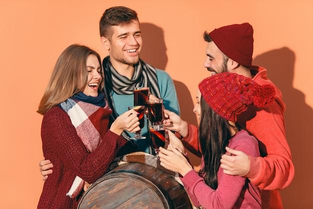 パーティーの写真撮影中にヨーロッパの男性と女性の笑顔。フォアグラウンドでホットグリューワインをワイングラスでスタジオフェストで友達を装った男。 無料写真