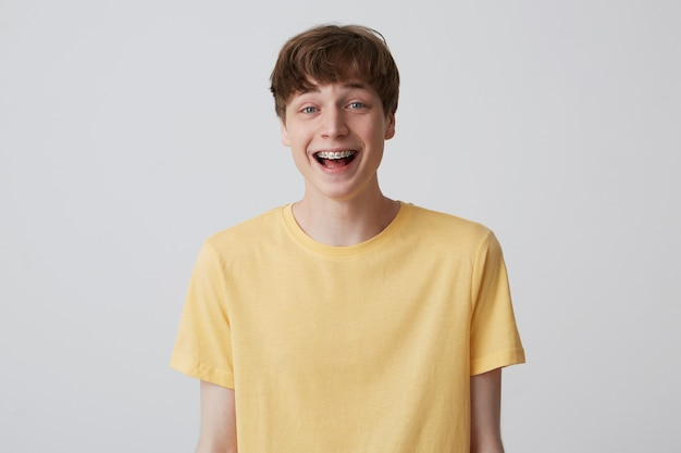 Smiling excited blond young man with short haircut and metal braces on teeth wears yellow t shirt and looks happy Free Photo