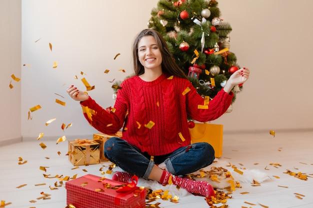 Улыбающаяся возбужденная красивая женщина в красном свитере сидит дома у елки, бросая золотые конфетти в окружении подарков и подарочных коробок Бесплатные Фотографии