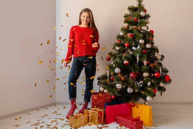 선물 및 선물 상자에 둘러싸인 황금 색종이를 던지고 크리스마스 트리에 집에 앉아 빨간 스웨터에 흥분된 예쁜 여자를 웃고 무료 사진