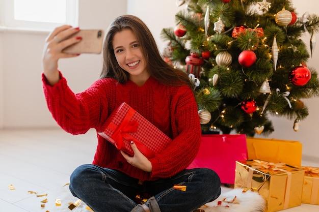 크리스마스 트리 풀고 선물 및 전화 카메라에 셀카 사진을 찍는 선물 상자에 집에 앉아 빨간 스웨터에 흥분된 예쁜 여자를 웃고 무료 사진